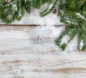O abeto nevado do Natal ramifica no fundo de madeira branco rústico imagens de stock royalty free