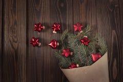 O abeto ramifica no papel de embalagem com as bolas vermelhas do Natal, w marrom Foto de Stock