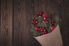 O abeto ramifica no papel de embalagem com as bolas vermelhas do Natal, w marrom Imagens de Stock