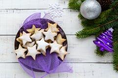 O abeto verde ramifica com cookies estrela-dadas forma em um fundo branco Tema do Natal Fotografia de Stock