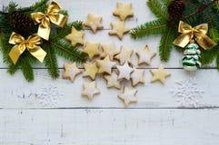 O abeto verde ramifica e decoração com curvas do ouro e as cookies estrela-dadas forma em um fundo branco Tema do Natal Imagens de Stock