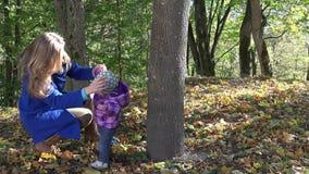 O abraço da mãe abraça sua filha do bebê perto do tronco de árvore no parque da estação do outono 4K video estoque