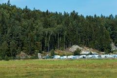 O acampamento completamente das caravana aproxima a floresta Fotos de Stock