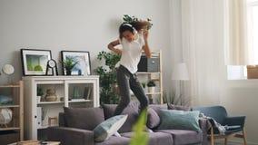 O adolescente afro-americano ativo está dançando no sofá que escuta a música através dos fones de ouvido e que tem o divertimento video estoque