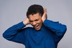 O adolescente afro-americano grita na raiva, cobrindo as orelhas imagem de stock