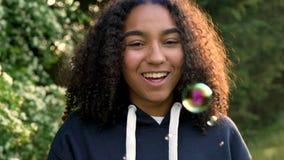 O adolescente afro-americano ou a jovem mulher da menina da raça misturada que riem, rindo e fundindo borbulham filme