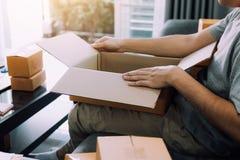 O adolescente asiático do empresário está abrindo uma caixa de cartão a fim pôr o produto que o cliente pediu na caixa a imagem de stock