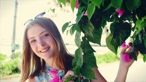 O adolescente bonito anda no ar fresco, aprecia a natureza e flores tropicais bonitas Vídeo conservado em estoque, lento-moviment vídeos de arquivo