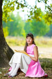 O adolescente bonito lê o livro sob enorme Fotografia de Stock