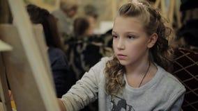 O adolescente bonito que senta-se na armação pinta uma imagem em uma escola de arte Escola de arte profissional para crianças filme