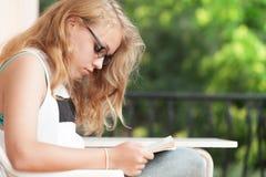O adolescente caucasiano louro leu um livro imagem de stock