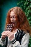 O adolescente com cabelo vermelho ama o chocolate foto de stock royalty free