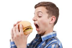 O adolescente com fome quer comer um Hamburger grande Fotos de Stock