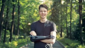 O adolescente com um braço protético biônico futurista está estando em um parque e está sorrindo na câmera