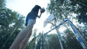 O adolescente com um braço robótico biônico está manipulando uma bola e está tentando bater a cesta