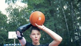 O adolescente com uma mão protética está jogando um basquetebol