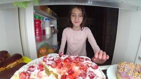 O adolescente da menina abre o refrigerador na noite Fome da noite glutonaria da dieta imagem de stock royalty free