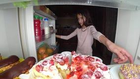 O adolescente da menina abre o refrigerador na noite Fome da noite glutonaria da dieta fotografia de stock