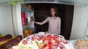 O adolescente da menina abre o refrigerador na noite Fome da noite glutonaria da dieta fotos de stock royalty free