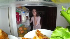 O adolescente da menina abre o refrigerador na noite Fome da noite glutonaria da dieta fotografia de stock royalty free
