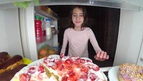 O adolescente da menina abre o refrigerador na noite Fome da noite glutonaria da dieta fotos de stock