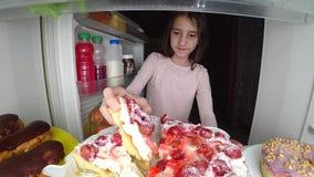 O adolescente da menina abre o refrigerador na noite Fome da noite glutonaria da dieta foto de stock royalty free
