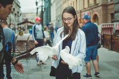 O adolescente da menina anda na rua de St Petersburg, realiza nas mãos dos pombos brancos foto de stock