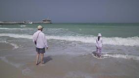 O adolescente da menina com paizinho entra nas ondas do mar do Golfo Pérsico na praia do vídeo da metragem do estoque de Dubai filme