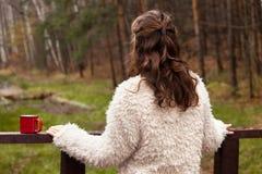 O adolescente da menina em um casaco de pele branco está em uma ponte de madeira, girando a de volta à câmera, olhando a floresta Fotografia de Stock Royalty Free
