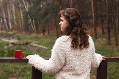 O adolescente da menina em um casaco de pele branco está em uma ponte de madeira, girando a de volta à câmera, olhando a floresta Imagens de Stock
