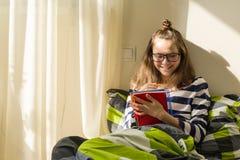 O adolescente da menina está estudando em casa Assento na escrita da cama no caderno da escola imagem de stock