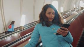 O adolescente da menina no metro subterrâneo monta em uma escada rolante, guarda o estilo de vida do smartphone morena da menina video estoque