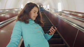 O adolescente da menina no metro subterr?neo monta em uma escada rolante, guarda o smartphone busca moreno da filha da menina filme