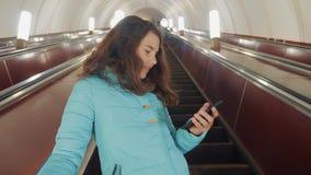O adolescente da menina no metro subterr?neo monta em uma escada rolante, guarda o smartphone busca moreno da filha da menina vídeos de arquivo