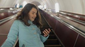 O adolescente da menina no metro subterr?neo monta em uma escada rolante, guarda o smartphone busca moreno da filha da menina video estoque
