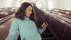 O adolescente da menina no metro subterr?neo monta em uma escada rolante, guarda o smartphone estilo de vida moreno da filha da m video estoque