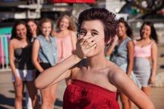 O adolescente de riso cobre sua boca fotografia de stock