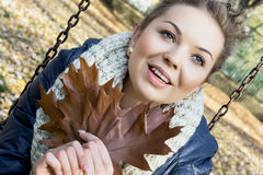 O adolescente de sorriso com carvalho marrom sae nas mãos Imagem de Stock