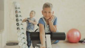 O adolescente de sorriso que faz o peso pesado exercita para o bíceps filme