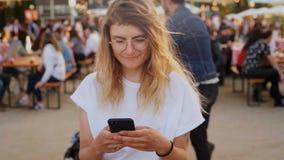 O adolescente do moderno no festival usa o smartphone video estoque