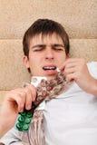 O adolescente doente toma um comprimido Fotografia de Stock