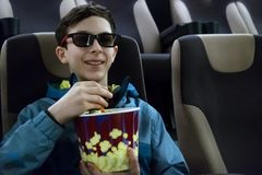 O adolescente em sorrisos dos vidros 3D ao olhar um filme da comédia O indivíduo europeu bonito em um revestimento senta-se em um imagem de stock royalty free