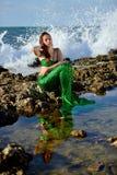 O adolescente em um traje da sereia está sentando-se com seus olhos fechados em uma rocha na praia contra o contexto de ondas rag foto de stock royalty free
