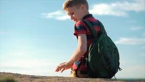 O adolescente em uma camisa vermelha com uma trouxa atrás dele, no por do sol, sentando-se em um monte alto, apreciando a naturez vídeos de arquivo