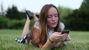 O adolescente emocional que encontra-se na grama verde usa o smartphone video estoque