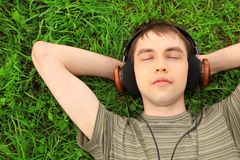 O adolescente encontra-se na grama nos auscultadores Fotos de Stock Royalty Free
