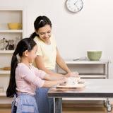 O adolescente ensina a irmã como amassar a massa de pão Fotos de Stock Royalty Free