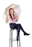 O adolescente está sentando-se na cadeira com guarda-chuva imagem de stock