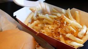O adolescente est? comendo batatas fritas fritadas com cebolas e queijo A m?o punciona uma forquilha pl?stica com alimento insalu vídeos de arquivo