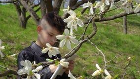 O adolescente faz o trabalho de laboratório da biologia no parque vídeos de arquivo